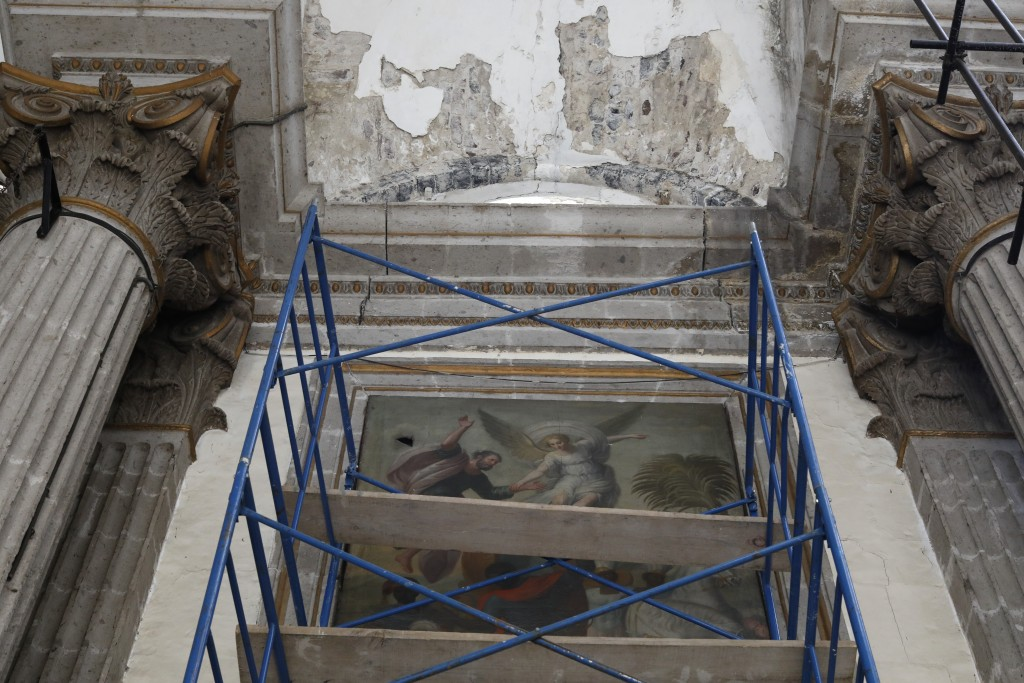 Scaffolding stands in front of a damaged painting and a section of the damaged vault, during the early stages of reconstruction work at Nuestra Senora...