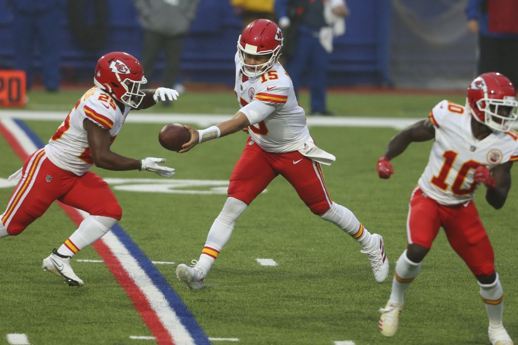 Kansas City Chiefs quarterback Patrick Mahomes, center, hands off the ball to Clyde Edwards-Helaire, left, during the first half of an NFL football ga...