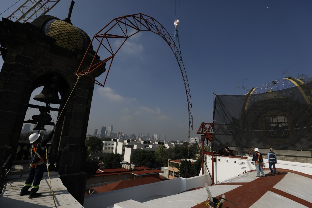 A worker guides a steel arch being lifted by a crane into place overtop the damaged cupola, as part of a frame that will support a temporary metal roo...