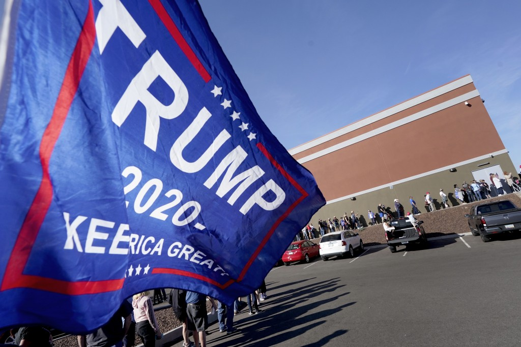 People wait in line for a shuttle to see President Donald Trump speak at a campaign rally, Monday, Oct. 19, 2020, in Prescott, Ariz. (AP Photo/Matt Yo...