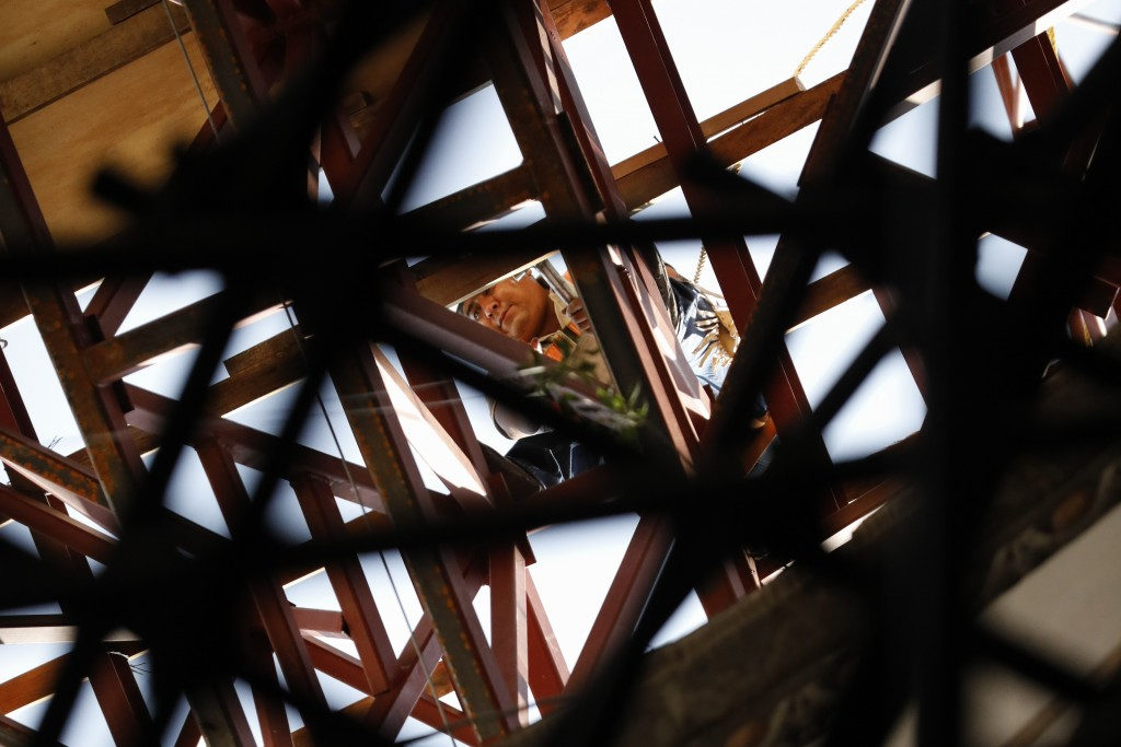 A worker picks his way across a steel frame at the base of the damaged cupola, during the early stages of reconstruction work at Nuestra Senora de Los...