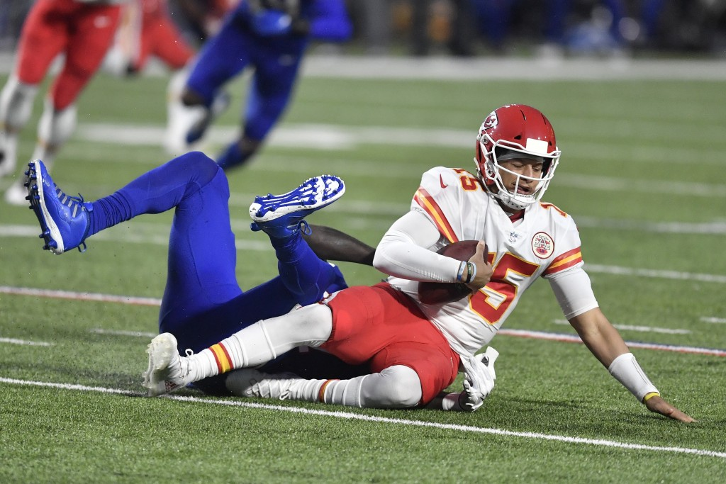 Kansas City Chiefs quarterback Patrick Mahomes, right, is sacked by Buffalo Bills' Mario Addison during the first half of an NFL football game, Monday...