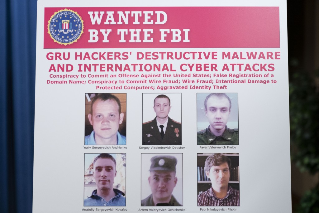 A poster showing six wanted Russian military intelligence officers is displayed before a news conference at the Department of Justice, Monday, Oct. 19...