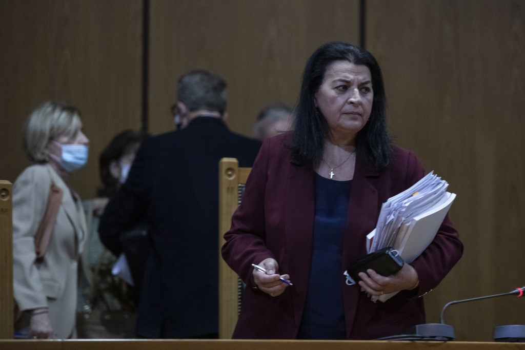 Presiding judge Maria Lepenioti, right, leaves the court during the Golden Dawn trial, in Athens, Tuesday, Oct. 20, 2020. A prosecutor has recommended...