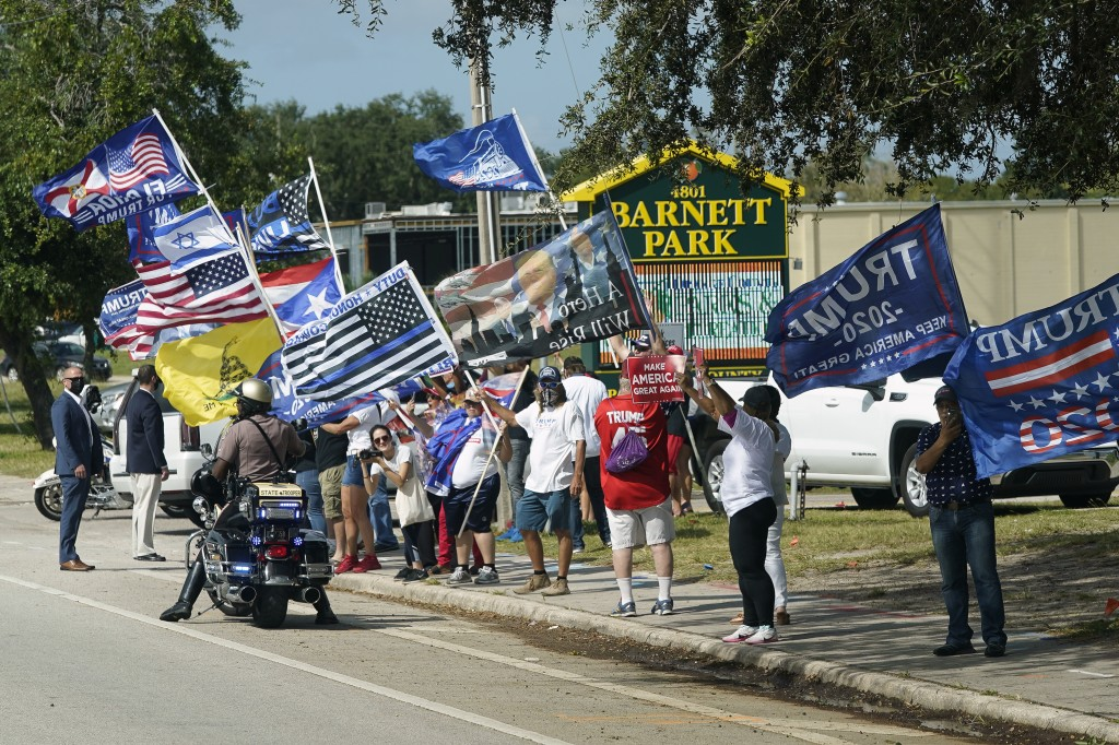 A group of President Donald Trump supporters wave flags along the street as Democratic vice presidential candidate Sen. Kamala Harris, D-Calif., arriv...