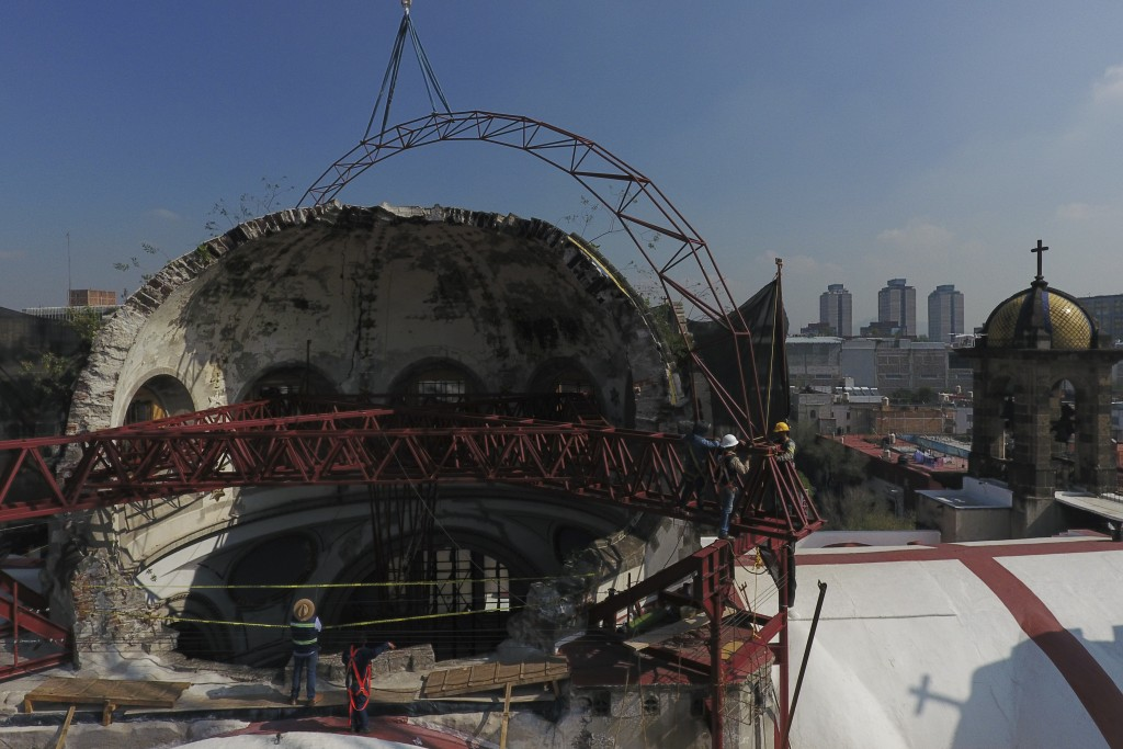 Workers guide into place a steel arch lowered by a crane, as part of a frame that will support a temporary metal roof overtop the damaged cupola, in t...