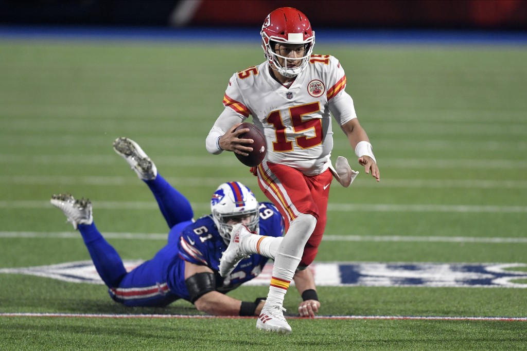 Kansas City Chiefs quarterback Patrick Mahomes (15) evades Buffalo Bills' Justin Zimmer during the second half of an NFL football game, Monday, Oct. 1...