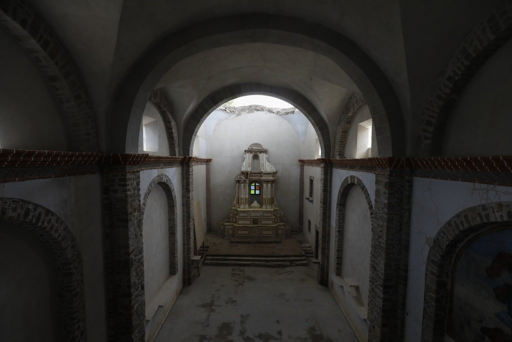 The damaged altar stands below a collapsed section of the vault, now shielded by a temporary metal roof, at the former San Guillermo Convent, where re...