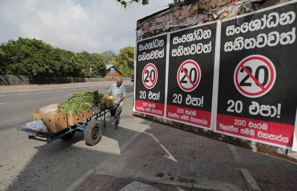 A Sri Lankan vegetable seller pushes his cart past posters against a proposed constitutional amendment that would consolidate power in the president's...