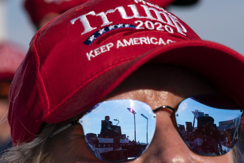 Reflected in a supporter's sunglasses, President Donald Trump speaks at a campaign rally at Tucson International Airport, Monday, Oct. 19, 2020, in Tu...