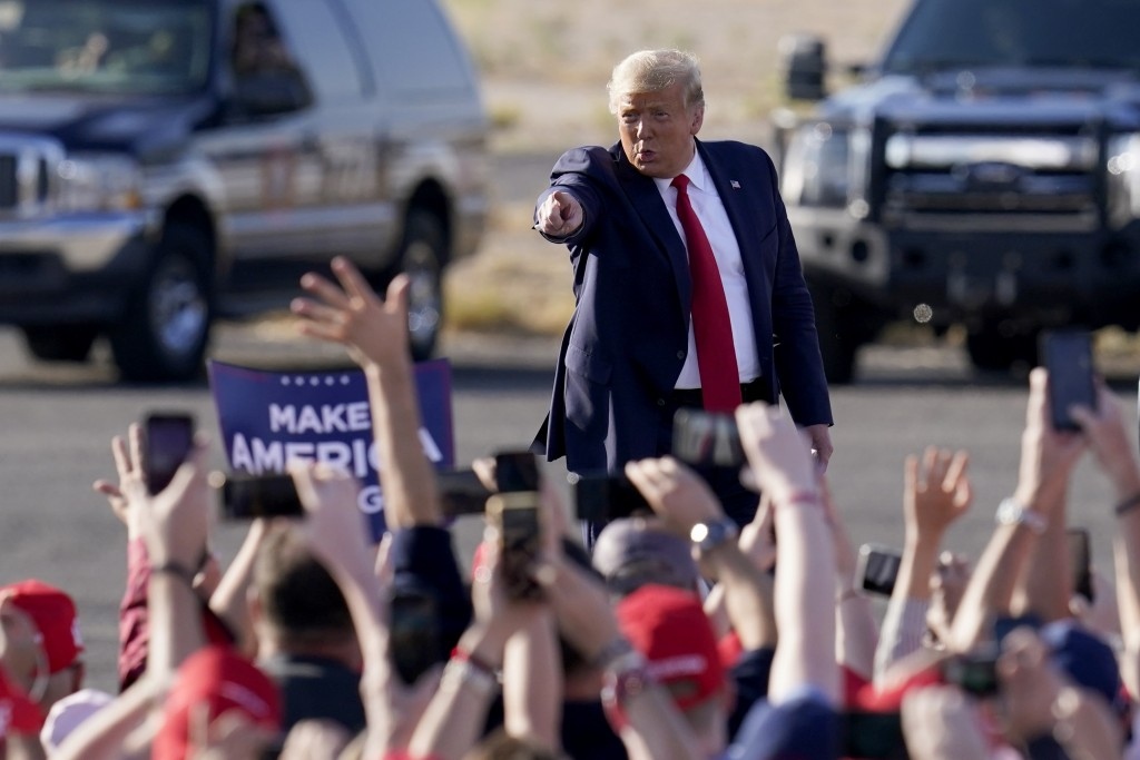 President Donald Trump waves to a cheering crowd as he arrives for a campaign rally Monday, Oct. 19, 2020, in Tucson, Ariz. (AP Photo/Ross D. Franklin...