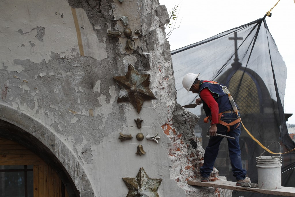 A worker seals a crack with a traditional mortar to keep loose pieces from falling from the damaged cupola, in the early stages of reconstruction work...
