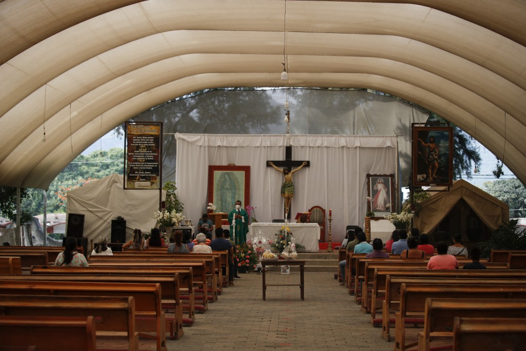 Father Filiberto Arias Araujo leads an afternoon Mass in a temporary outdoor chapel erected outside the former San Juan Bautista Convent, where restor...