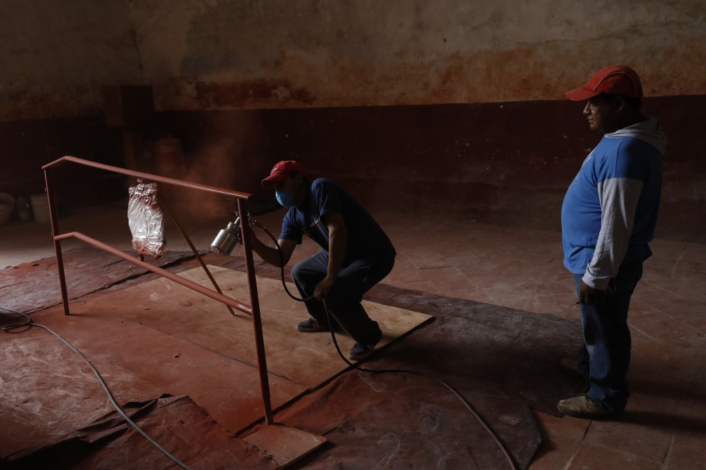 A worker sprays primer onto a railing inside the former San Juan Bautista Convent, where restoration work is underway following damage in a 2017 earth...