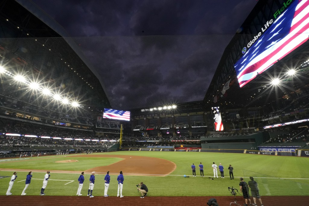 Members of the Los Angeles Dodgers stand during the national anthem before Game 7 of a baseball National League Championship Series Sunday, Oct. 18, 2...