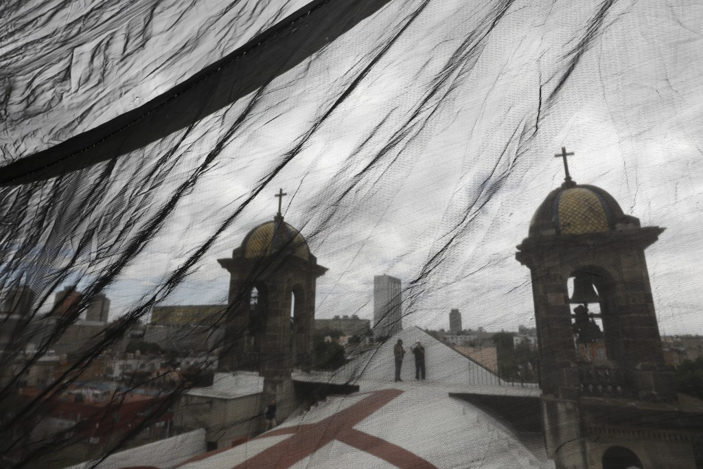 Men are seen through safety netting as they stand atop a less-damaged section of Nuestra Senora de Los Angeles, or Our Lady of Angels church, during t...