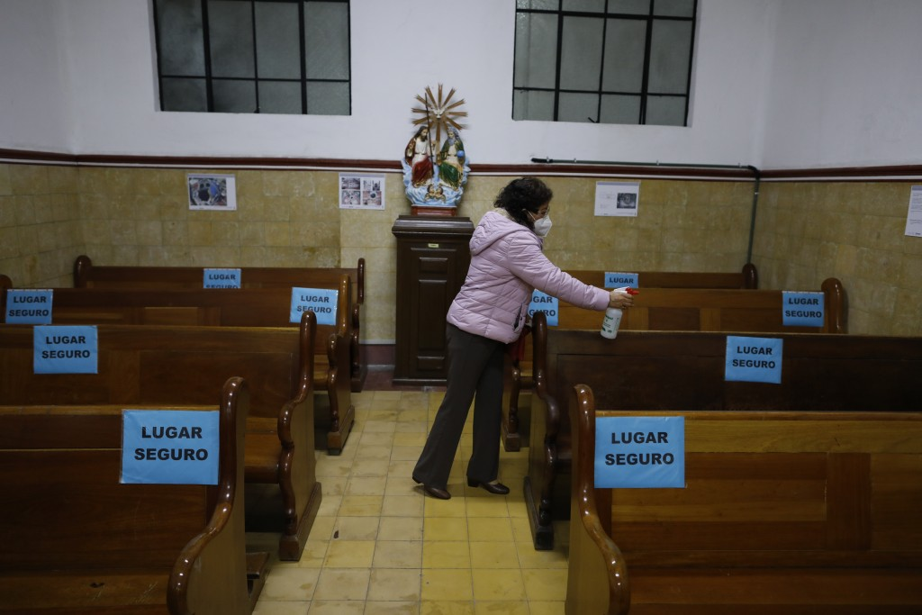 A parishioner sprays disinfectant on pews, marked with signs to encourage social distancing, ahead of Mass in a provisional chapel adjacent to the Nue...