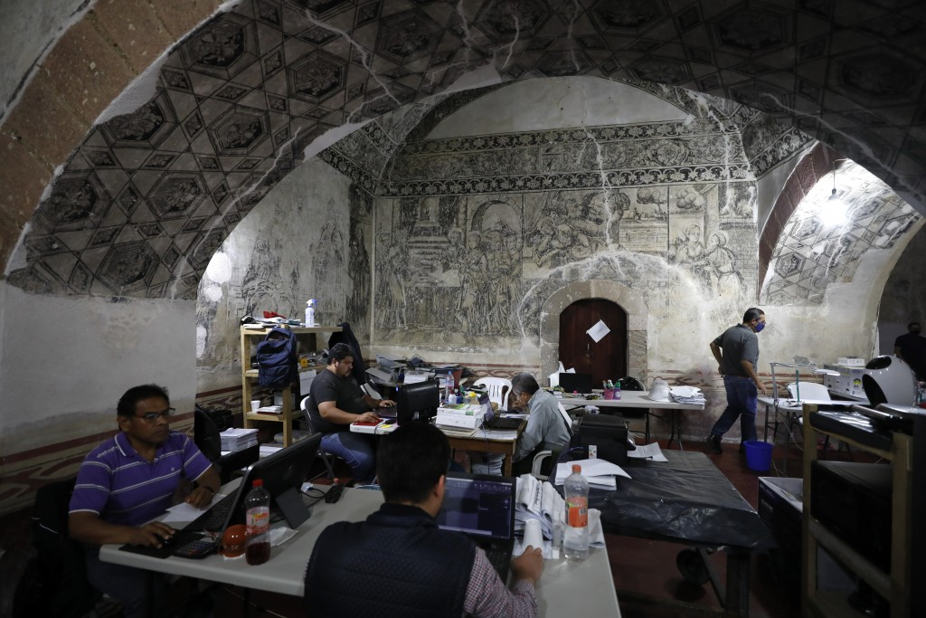 Employees of the construction company entrusted with the restoration of the former San Juan Bautista Convent work at desks set up beneath painted vaul...