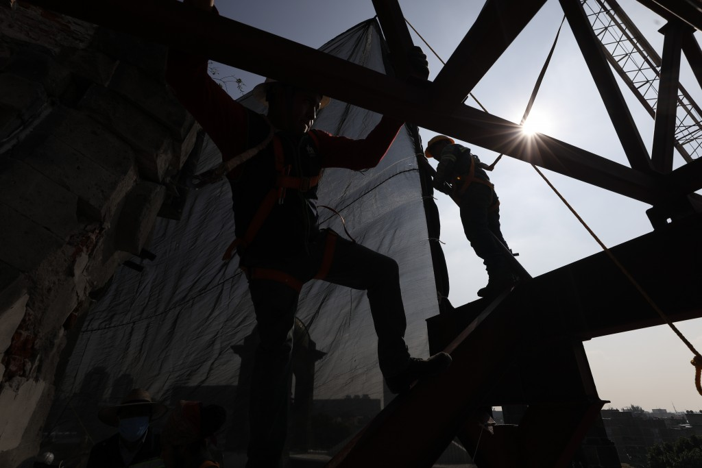 Workers climb on a metal frame beside the damaged cupola, in the early stages of reconstruction work at Nuestra Senora de Los Angeles, or Our Lady of ...