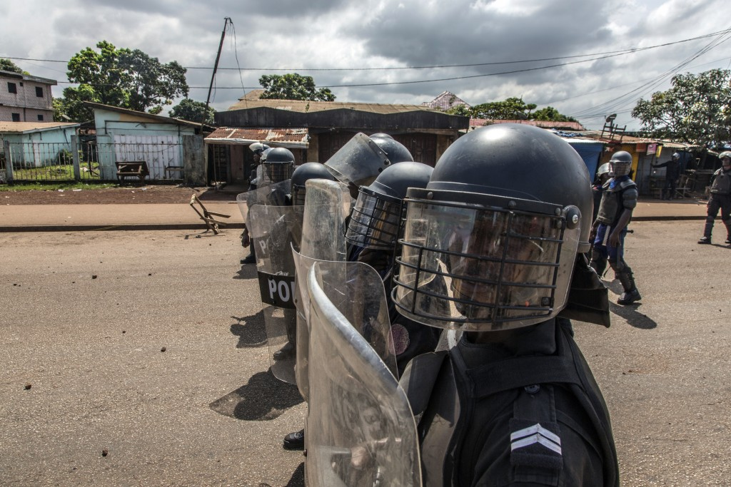Police face supporters of Guinean opposition leader Cellou Dalein Diallo in Conakry, Guinea, Wednesday, Oct. 21, 2020. Diallo declared himself winner ...