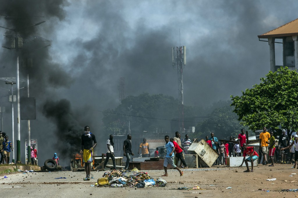 Supporters of Guinean opposition leader Cellou Dalein Diallo clash with police in Conakry, Guinea, Wednesday, Oct. 21, 2020. Diallo declared himself w...
