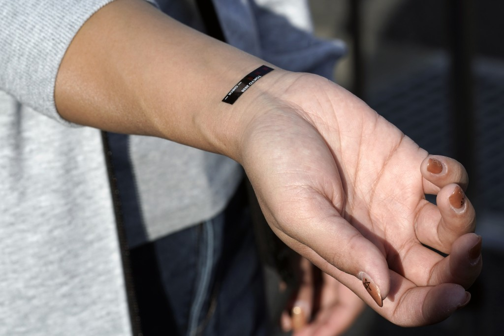 A participant shows a body temperature sticker during a screening test for spectators and officials to ensure a safe and secure Toyo Olympic Games Wed...