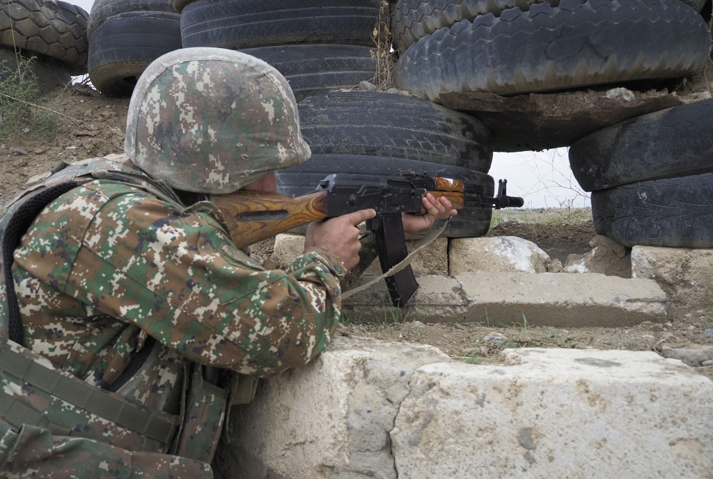An Ethnic Armenian soldier holds a Kalashnikov machine gun as he looks toward Azerbaijan's positions from a dugout at a fighting position on the front...