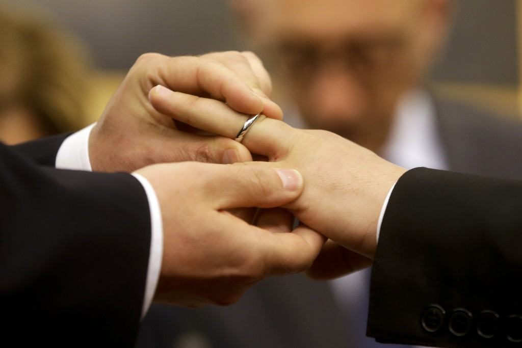 FILE - In this May 21, 2015 file photo, Mauro Cioffari, left, puts a wedding ring on his partner Davide Conti's finger as their civil union is being r...