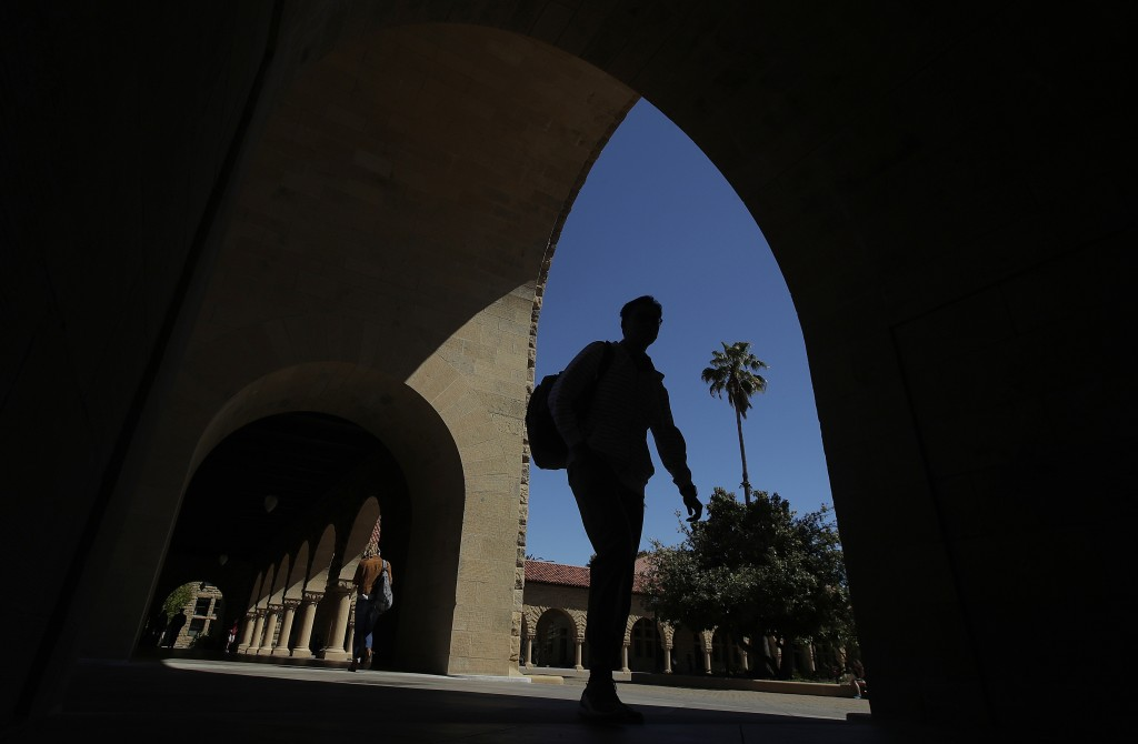 FILE - In this April 9, 2019, file photo, pedestrians walk on the campus at Stanford University in Stanford, Calif. The Education Department released ...