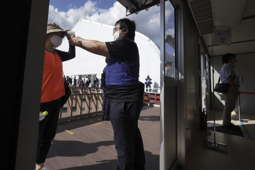A staff member checks a body temperature in a screening test for spectators and officials to ensure a safe and secure Toyo Olympic Games Wednesday, Oc...