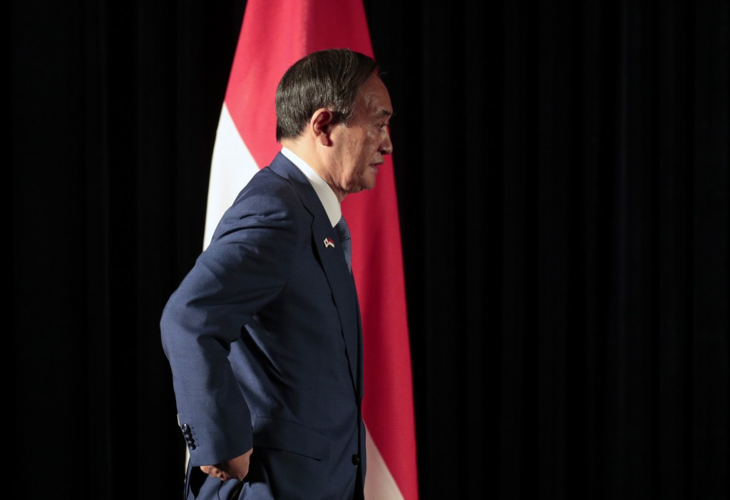 Japanese Prime Minister Yoshihide Suga walks past Indonesian national Red-White flag as he arrives for a press conference in Jakarta, Indonesia, Wedne...