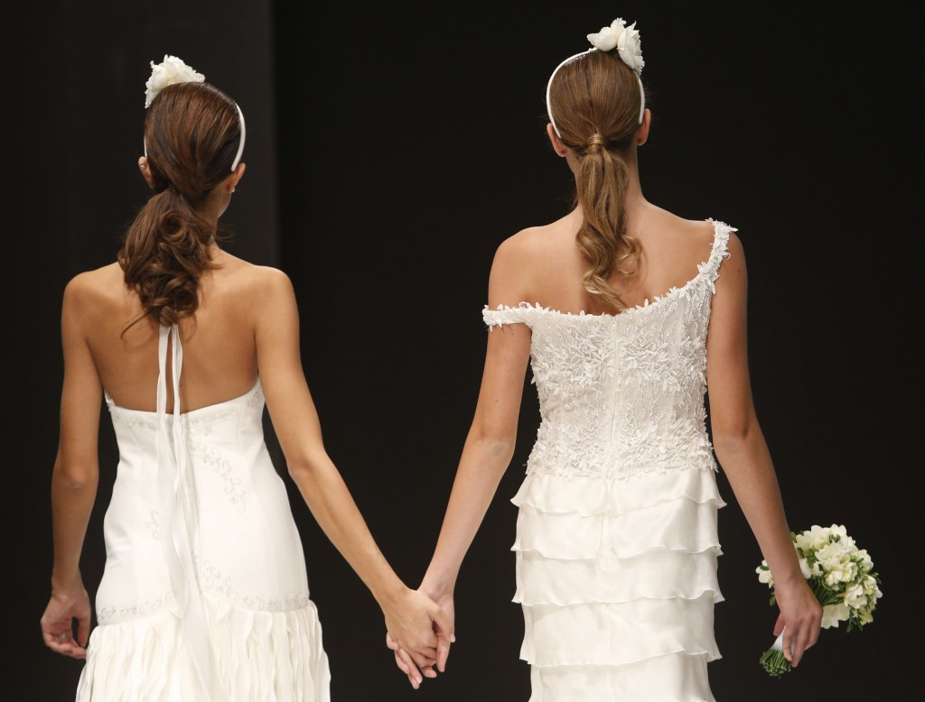 """FILE -- In this Thursday, Oct. 23, 2014 file photo, models hold hands on the catwalk during a wedding fashion show with same-sex couples, dubbed """"The ..."""