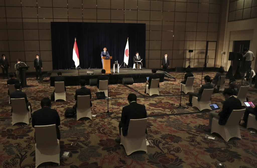 Japanese Prime Minister Yoshihide Suga speaks as members of the media sit spaced apart to maintain physical distancing during a press conference in Ja...