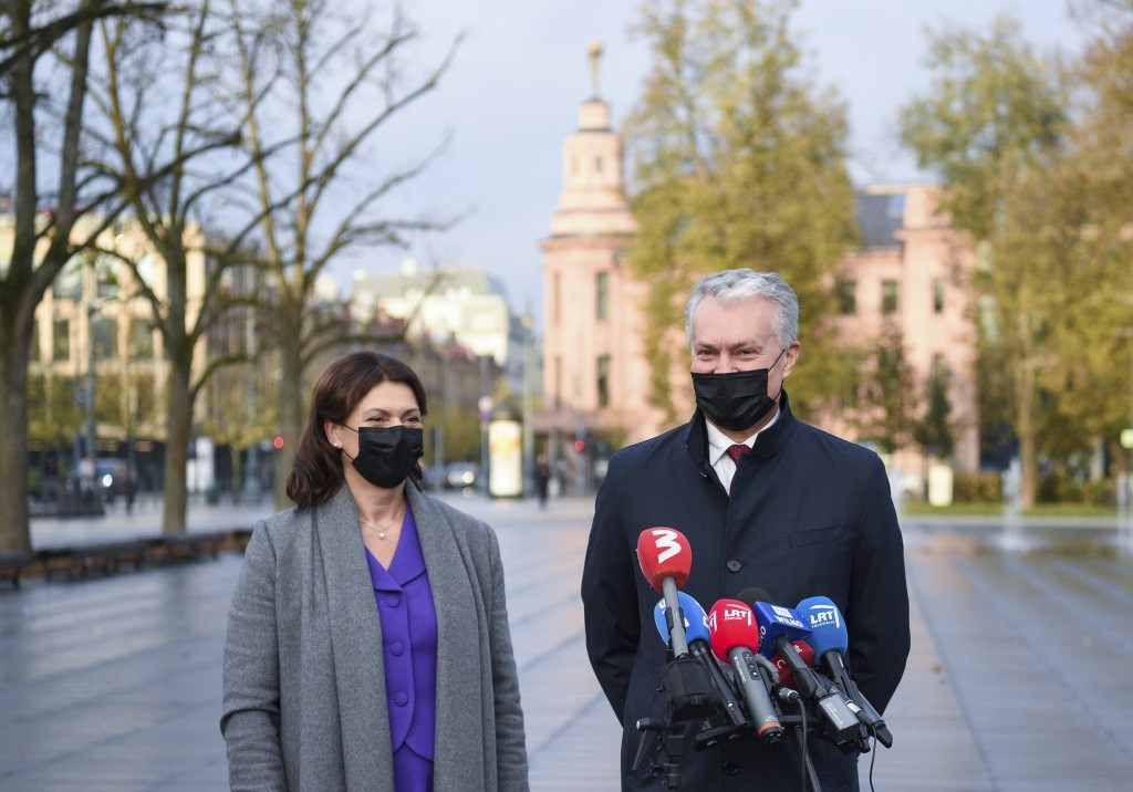 Lithuania's President Gitanas Nauseda, right, with his wife Diana Nausediene, wearing face masks to protect against coronavirus, speaks to the media a...