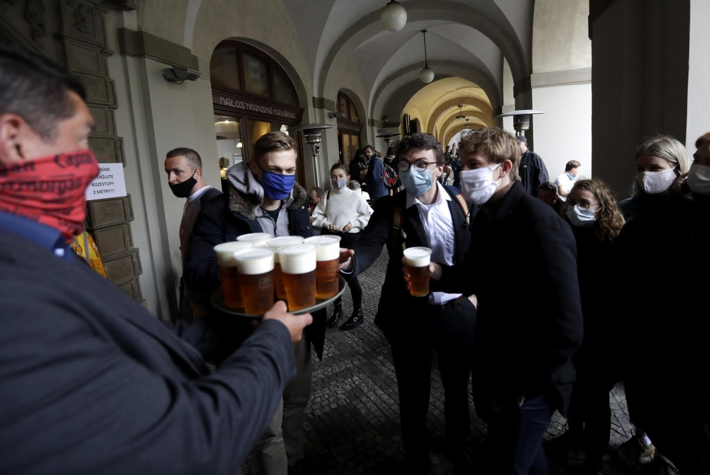 FILE - In this file photo people line up for a beer at a restaurant terrace in Prague, Czech Republic, Monday, May 11, 2020. (AP Photo/Petr David Jose...