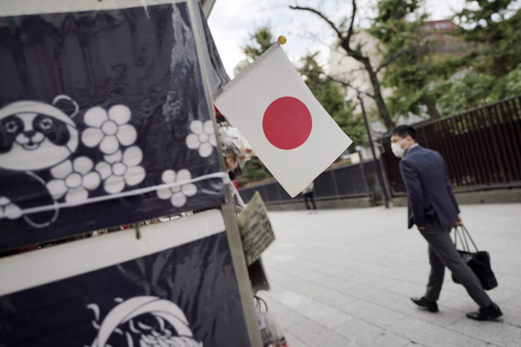 A man wearing a protective mask to help curb the spread of the coronavirus walks near a Japanese flag at a shopping arcade at Asakusa district Thursda...