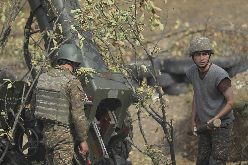 Ethnic Armenian soldiers fire an artillery piece at a fighting position on the front line, during a military conflict against Azerbaijan's armed force...