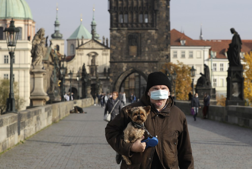 A man wearing a face mask carries his dog across the medieval Charles Bridge in Prague, Czech Republic, Wednesday, Oct. 21, 2020. In another desperate...