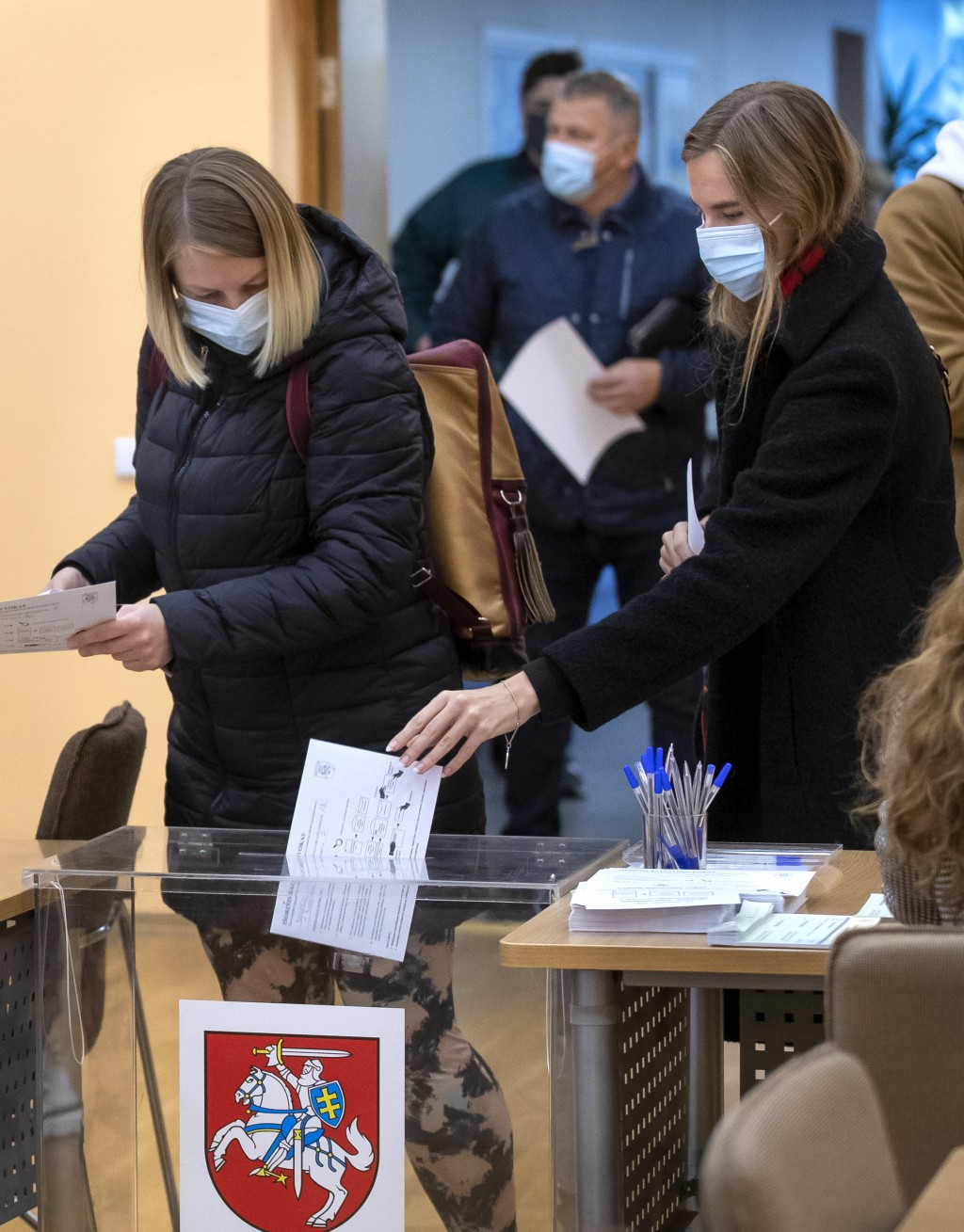 People wearing face masks to protect against coronavirus, vote at a polling station during early voting in the second round of a parliamentary electio...