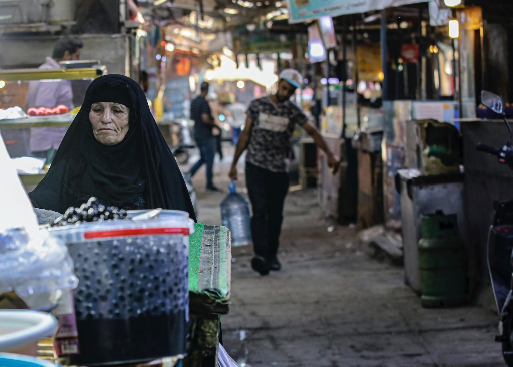 A woman street vendor waits for customers in Basra, Iraq, Wednesday, Oct. 21, 2020.   Iraq is in the throes of an unprecedented liquidity crisis, as t...