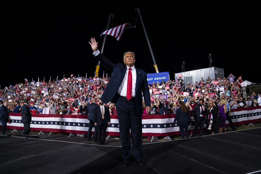 President Donald Trump waves to the crowd as he walks off stage after speaking at a campaign rally at Gastonia Municipal Airport, Wednesday, Oct. 21, ...