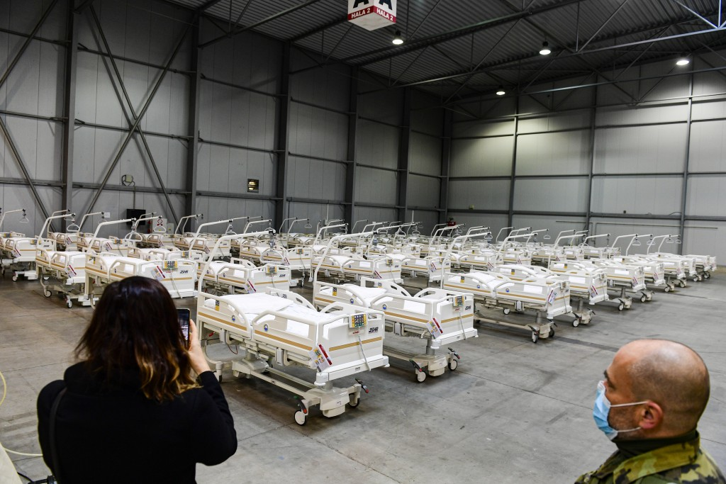 A journalist takes a picture of beds prepared in a field hospital, which will function as a backup device for patients with coronavirus, in the Letnan...