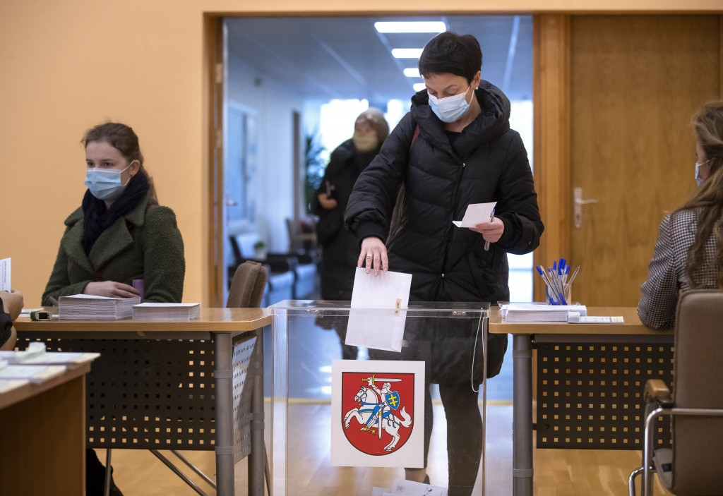 A Lithuanian woman, wearing face masks to protect against coronavirus, casts her ballot at a polling station during early voting in the second round o...
