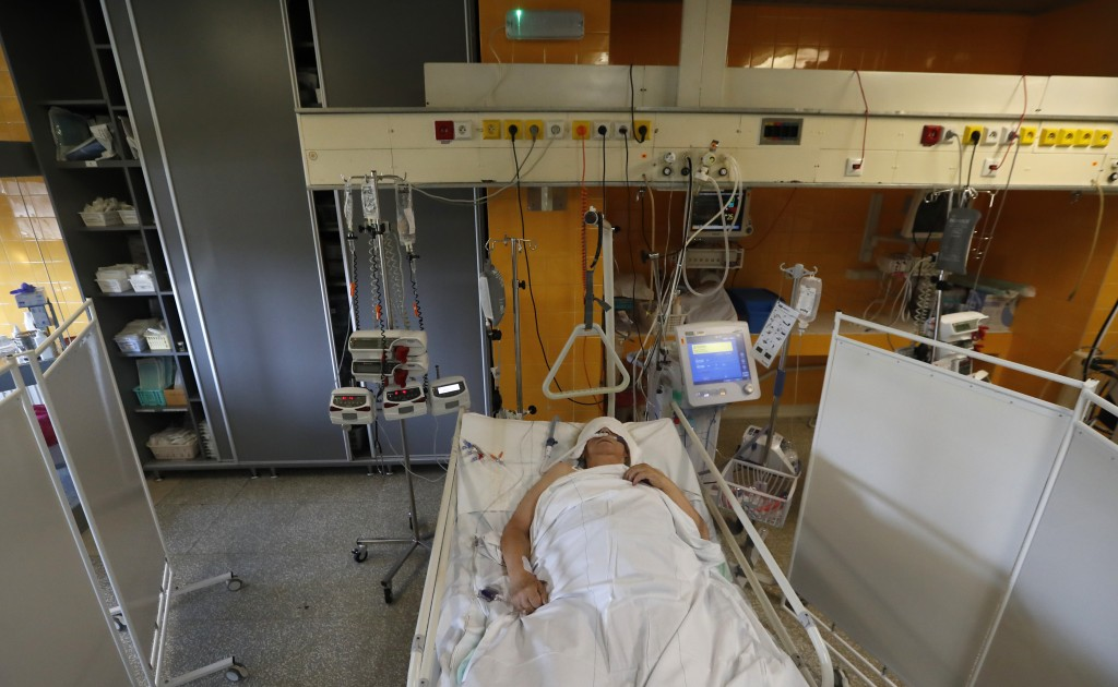 FILE - In this Oct. 1, 2020 file photo a COVID-19 patient lies on a bed in an intensive care unit (ICU) at Na Bulovce hospital in Prague, Czech Republ...