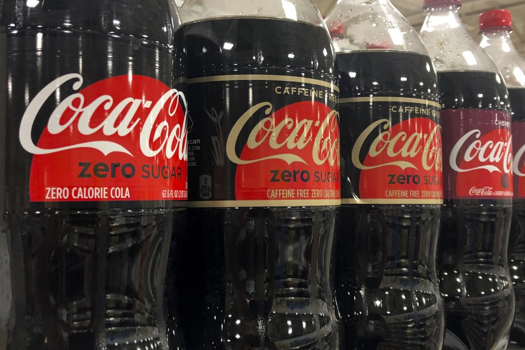 Bottles of Coca-Cola products are shown, Tuesday, Oct. 20, 2020, at a store in Dania Beach, Fla. The Coca-Cola Co. said it saw gradual improvement in ...