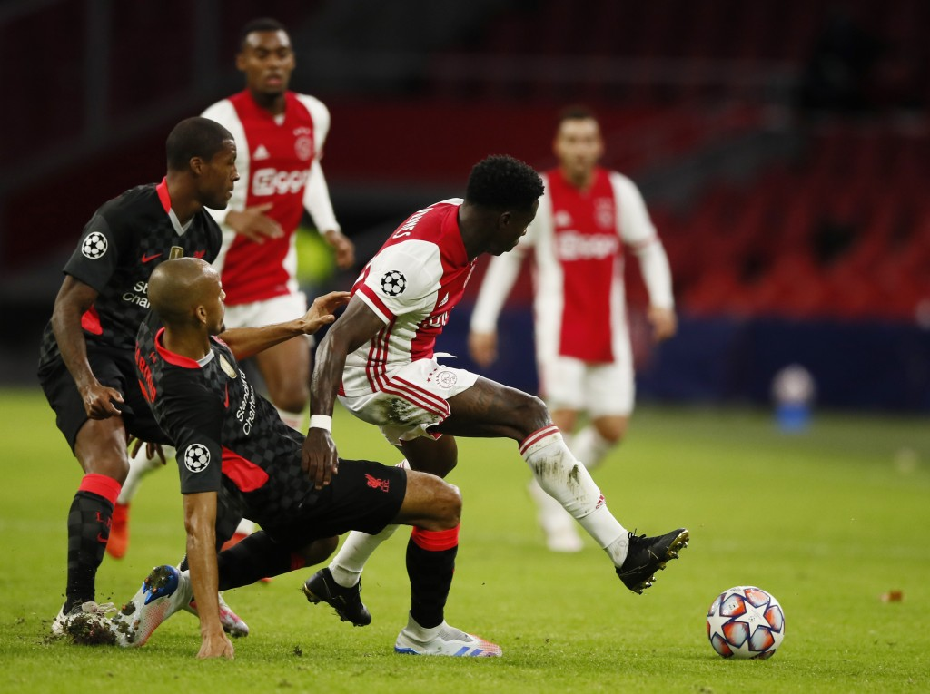 Liverpool's Fabinho, left, tries to stop Ajax's Quincy Promes during the group D Champions League soccer match between Ajax and Liverpool at the Johan...
