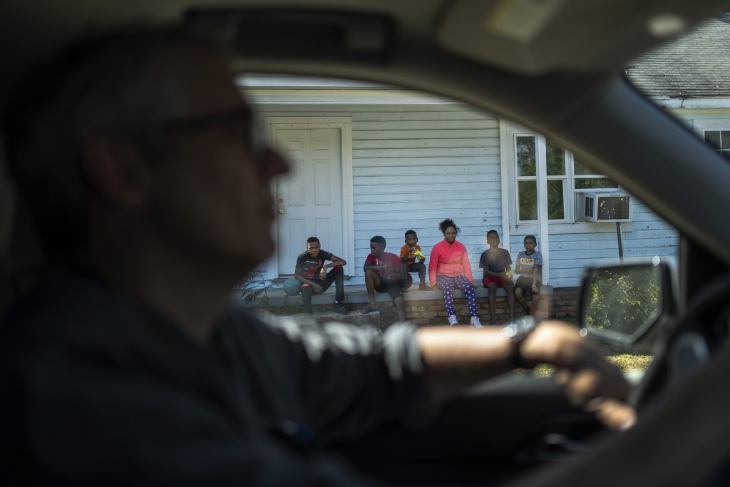 A family sits on their front porch seen through a vehicle in Meridian Miss., Monday, Oct. 5, 2020. (AP Photo/Wong Maye-E)