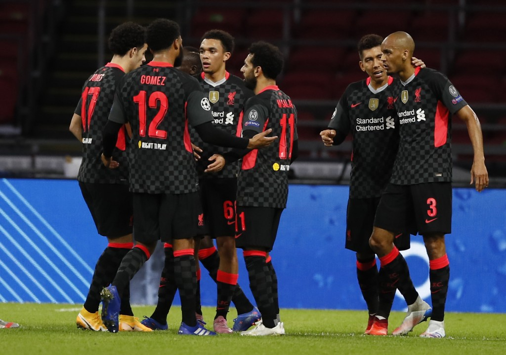 Liverpool's Trent Alexander-Arnold, center, no 66, celebrates with teammates after scoring during the group D Champions League soccer match between Aj...