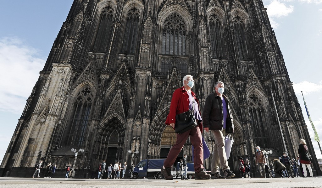 People are ordered to wear face masks in front of the famous Cathedral in Cologne, Germany, Thursday, Oct. 22, 2020. The city exceeded the important w...