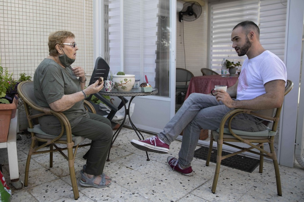 Israeli Itamar Glazer, right, sits with 85-year-old Holocaust survivor Sara Weinsten during a visit in Yavne, Israel, Thursday, Oct. 8, 2020. For thou...
